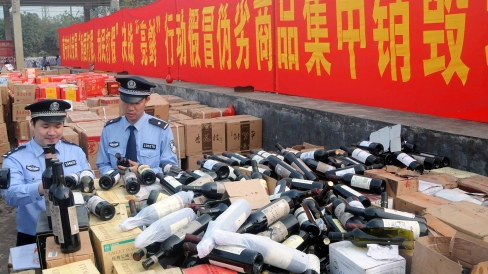 Huge stockpiles of fake premium spirits and wines are tracked down during a campaign against fakes, Nanning, southwest Chinas Guangxi Zhuang Autonomous Region, 6 November 2011. Nearly 200 mainland cities publicly destroyed tens of millions of fake and substandard goods on 6 November as part of a major publicity drive intended to rein in the countrys booming counterfeiting industry. More than 25 million items were confiscated by police as part of Operation Draw the Sword - a campaign which, according to Xinhua, is also aimed at thwarting the production of imitation designer clothes, fake cosmetics and foodstuffs.